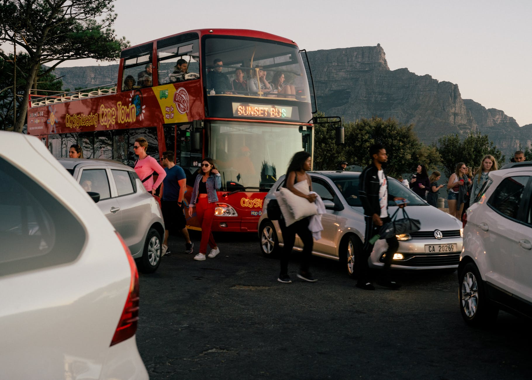 cars and tourist bus and people in mountains
